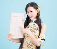 Muchacha asiática en qipao del cheongsam con el libro chino Imágenes de archivo libres de regalías