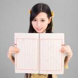 Muchacha asiática en qipao del cheongsam con el libro chino Foto de archivo