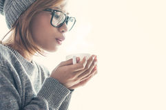 Muchacha asiática en ropa de lana con una taza de bebida caliente foto de archivo