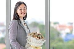 Muchacha asiática en un traje que se coloca en la sonrisa de la ventana feliz con c fotos de archivo libres de regalías
