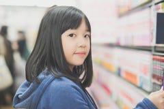 Muchacha asiática en una librería Fotos de archivo