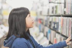 Muchacha asiática en una librería Imagen de archivo