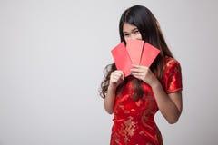 Muchacha asiática en vestido chino del cheongsam con el sobre rojo Imagenes de archivo
