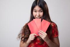 Muchacha asiática en vestido chino del cheongsam con el sobre rojo Fotos de archivo