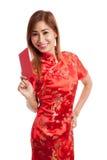 Muchacha asiática en vestido chino del cheongsam con el sobre rojo Foto de archivo libre de regalías
