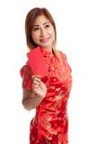 Muchacha asiática en vestido chino del cheongsam con el sobre rojo Imagen de archivo
