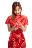 Muchacha asiática en vestido chino del cheongsam con el sobre rojo Imágenes de archivo libres de regalías