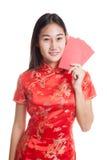 Muchacha asiática en vestido chino del cheongsam con el sobre rojo Imagen de archivo libre de regalías