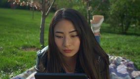 Muchacha asiática encantadora con PC de la tableta en parque de la primavera metrajes