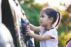 Muchacha asiática feliz del niño que se divierte a ayudar a parent el coche que se lava Imagen de archivo libre de regalías