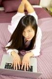 Muchacha asiática feliz en cama con PC Imagen de archivo libre de regalías