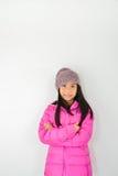 Muchacha asiática feliz que agota la chaqueta rosada que se sienta en gris Foto de archivo libre de regalías