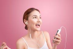 Muchacha asiática feliz que baila y que escucha la música aislada encendido imagenes de archivo
