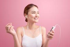 Muchacha asiática feliz que baila y que escucha la música aislada encendido foto de archivo libre de regalías