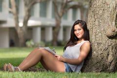 Muchacha asiática feliz que estudia debajo de un árbol en campus de la escuela Fotografía de archivo