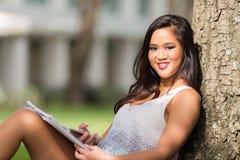 Muchacha asiática feliz que estudia debajo de un árbol en campus de la escuela Imágenes de archivo libres de regalías