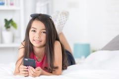 Muchacha asiática feliz que lee el teléfono elegante con la cara de la sonrisa en cama Fotografía de archivo libre de regalías