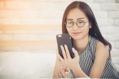 Muchacha asiática feliz que lee el teléfono elegante con la cara de la sonrisa en cama Foto de archivo libre de regalías