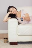 Muchacha asiática feliz que miente en el sofá que ve la TV Foto de archivo