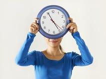 Muchacha asiática feliz que sostiene el reloj azul grande Fotos de archivo libres de regalías