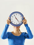 Muchacha asiática feliz que sostiene el reloj azul grande Imagen de archivo