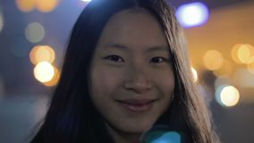 Muchacha asiática feliz que tira de las caras para la cámara, sonriendo y divirtiéndose, buena actriz almacen de video