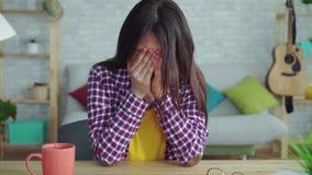 Muchacha asiática hermosa cansada y triste con el pelo largo en la sala de estar de un hogar moderno usando redes sociales en almacen de video