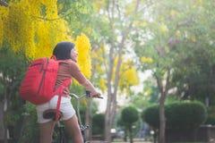 Muchacha asiática hermosa con la bicicleta roja del montar a caballo de la mochila Imagen de archivo