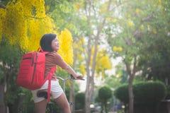 Muchacha asiática hermosa con la bicicleta roja del montar a caballo de la mochila en el parque Fotografía de archivo