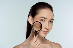 muchacha asiática hermosa con la piel pura que lleva a cabo concepto del cuidado de piel de la lupa imagenes de archivo