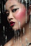 Muchacha asiática hermosa con maquillaje brillante detrás del vidrio y de los descensos de la cera Cara de la belleza Foto de archivo libre de regalías