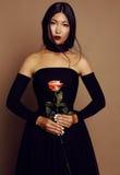 Muchacha asiática hermosa de la mirada con el pelo negro que lleva el vestido elegante Imágenes de archivo libres de regalías