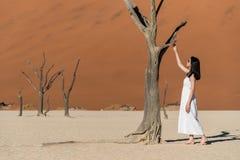 Muchacha asiática hermosa joven en el vestido blanco que se coloca en deadvlei, Fotografía de archivo libre de regalías