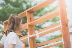 Muchacha asiática hermosa paiting el estante de madera por el rodillo Imagenes de archivo