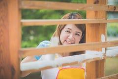 Muchacha asiática hermosa paiting el estante de madera por el rodillo Imagen de archivo libre de regalías