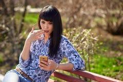 Muchacha asiática hermosa que se sienta en banco en parque con el teléfono a disposición mucho sorprendido imagenes de archivo