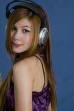 Muchacha asiática joven atractiva con los auriculares Fotos de archivo libres de regalías