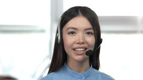Muchacha asiática joven caucásica que habla por las auriculares metrajes