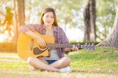 Muchacha asiática joven con la guitarra Foto de archivo