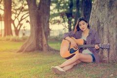 Muchacha asiática joven con la guitarra Imagen de archivo