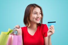 Muchacha asiática joven con la tarjeta y los panieres de crédito Foto de archivo libre de regalías