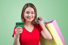 Muchacha asiática joven con la tarjeta y los panieres de crédito Imagen de archivo