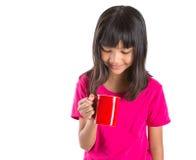 Muchacha asiática joven con la taza roja II Fotografía de archivo