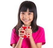 Muchacha asiática joven con la taza roja VII Foto de archivo libre de regalías