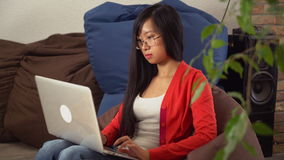 Muchacha asiática joven del retrato que mira con sonrisa la cámara y que charla en línea metrajes