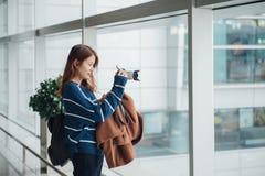 Muchacha asiática joven del viajero con la mochila que toma una foto con su cámara digital imagen de archivo libre de regalías