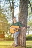Muchacha asiática joven en bosque con la guitarra Fotos de archivo libres de regalías