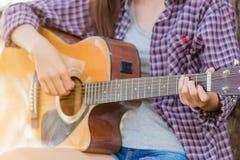 Muchacha asiática joven en bosque con la guitarra Imagen de archivo