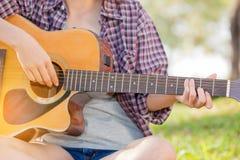 Muchacha asiática joven en bosque con la guitarra Imagen de archivo libre de regalías
