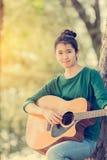 Muchacha asiática joven en el bosque que toca la guitarra Fotos de archivo